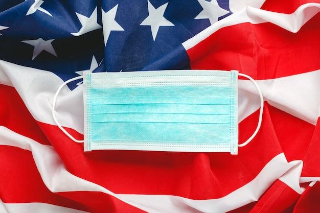Coronavírus nos eua. máscara protetora cirúrgica na bandeira nacional americana. covid-19