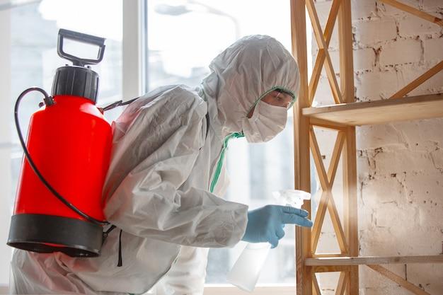 Coronavirus pandemic a desinfetante em um traje de proteção e uma máscara pulveriza desinfetantes