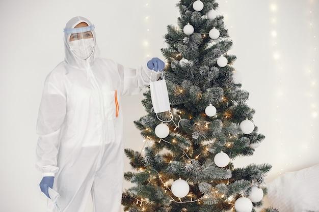 Coronavirus pandemic covid-2019. traje de proteção, googles, luvas, máscara. árvore de natal decorada com máscara médica.