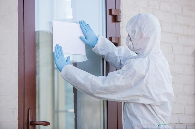 Coronavirus pandemic um desinfetante em uma roupa de proteção e máscara fazendo sinal de alerta