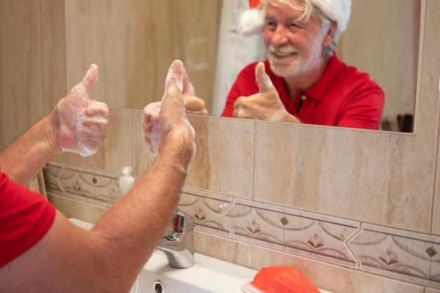 Coronavírus. um homem feliz sênior com chapéu de papai noel lava as mãos em casa gesticulando um sinal de ok com a mão. máscara cirúrgica vermelha para prevenir infecção por coronavírus na pia