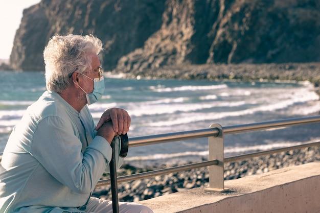 Coronavírus. velho barbudo sentado na praia sob a luz do pôr do sol segurando uma bengala por causa de dores no corpo