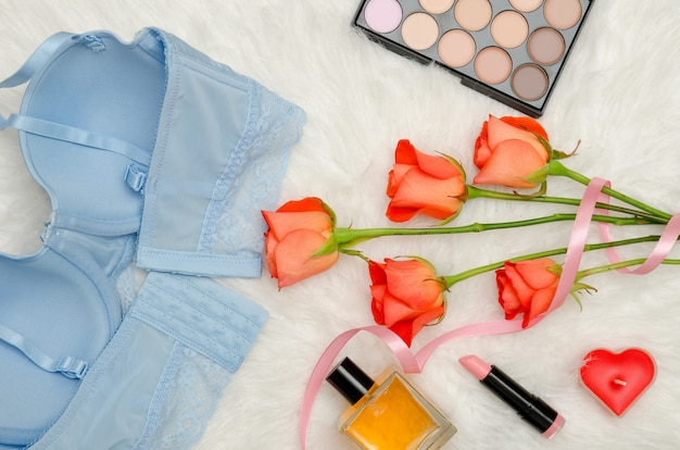 Corpete azul com renda, vista interna. pele branca, rosas alaranjadas e cosméticos