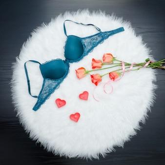 Corpete esmeralda com laço em pêlo branco. rosas laranja e velas em forma de coração vermelho.