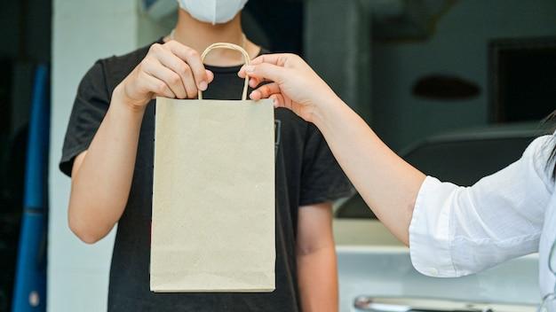Corpo a corpo peça produtos e alimentos entregues em casa para impedir a transmissão do coronavírus ou da covid-19.