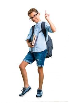 Corpo cheio do menino do estudante com trouxa e vidros que conta o número um. de volta à escola