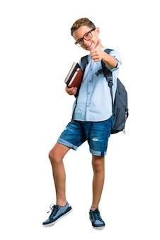 Corpo cheio do menino do estudante com trouxa e vidros que dá os polegares acima. de volta à escola