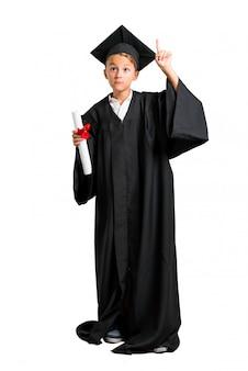 Corpo cheio do rapaz pequeno que gradua-se contando o sinal do número um no fundo branco isolado