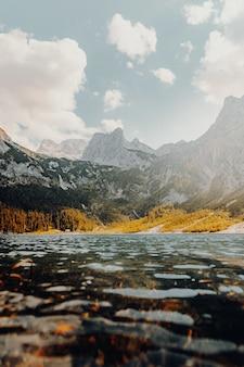 Corpo d'água observando a montanha sob o céu branco e azul durante o dia