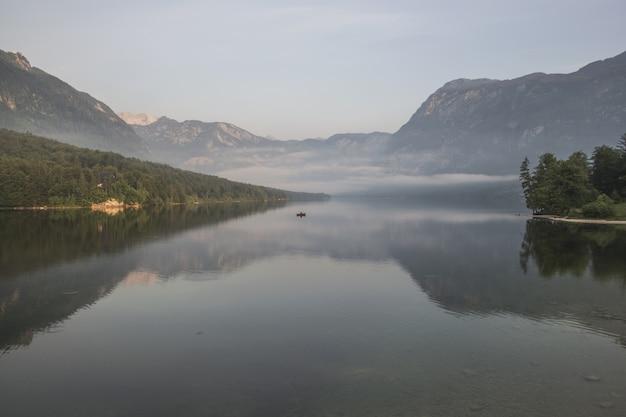 Corpo de água perto de cadeias de montanhas com vegetação verde coberta de névoa durante o dia