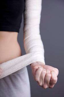 Corpo de menina forte com bandagem elástica na mão.