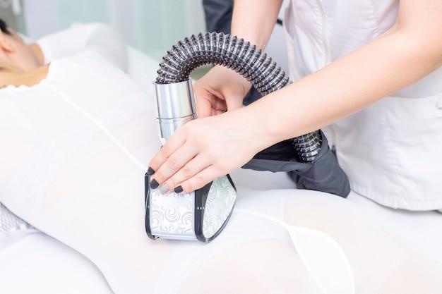 Corpo de menina glp massagem no spa. a menina recebe uma massagem de hardware, ela está usando um macacão especial para massagem. cavitação, celulite, perda de gordura. massagem com rolo a vácuo. manípulo