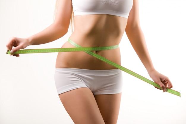 Corpo de mulher jovem em shorts brancos e top medindo a cintura com fita métrica nas mãos sobre fundo branco
