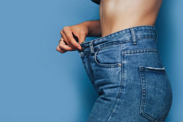 Corpo de mulher magra com calça jeans solta, corpo leve com roupas soltas