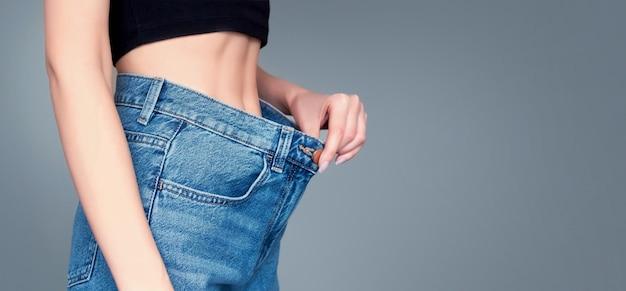 Corpo de mulher magra em grandes jeans em um fundo cinza