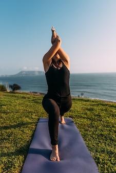 Corpo de mulher que entrelaça os braços voltados para o céu em um exercício de ioga para em seu colchonete fora de um parque em frente ao mar