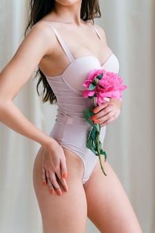 Corpo de uma linda garota magra em roupa interior segurando flores