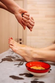 Corpo e pele. mestre profissional diligent embebendo óleo médico nos pés do cliente durante o procedimento