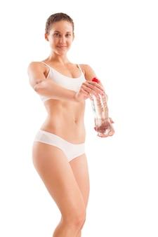 Corpo esguio de mulher com garrafa de água em branco.