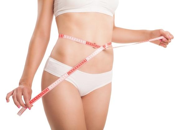 Corpo esguio de mulher com uma fita métrica.