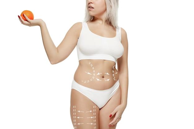 Corpo feminino com as setas de desenho. conceito de perda de gordura, lipoaspiração e remoção de celulite. marcas na mulher antes da cirurgia plástica. a imagem não é retocada na forma do corpo