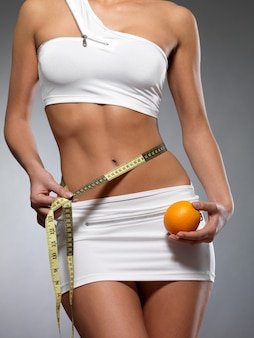 Corpo feminino de beleza com fita métrica e laranja. cocnept estilo de vida saudável.
