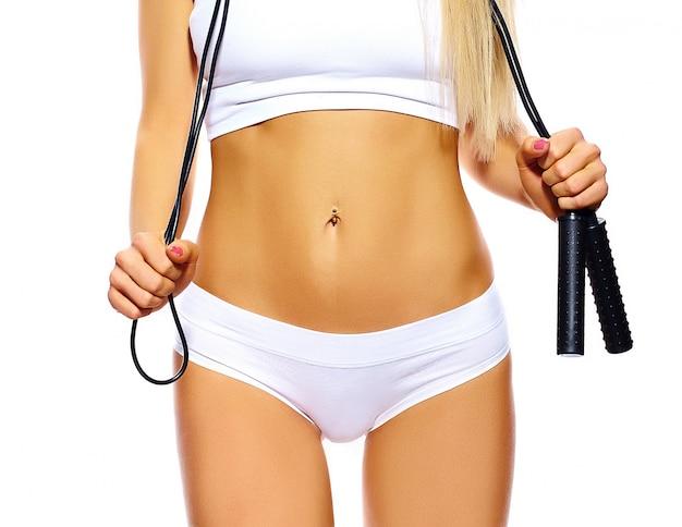 Corpo feminino de esporte sensual perfeita garota em lingerie branca com pular corda