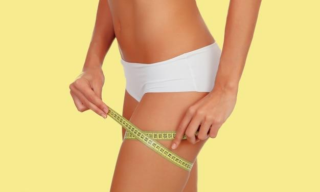 Corpo feminino sensual com biquíni e fita métrica