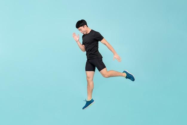 Corpo inteiro de energético jovem atleta homem asiático pulando