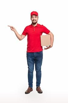 Corpo inteiro de entregador positivo de camisa vermelha e boné carregando caixa de papelão e apontando para o espaço vazio