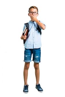 Corpo inteiro de estudante menino com mochila e óculos cobrindo a boca com as mãos