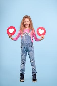 Corpo inteiro de menina adolescente positiva em jeans casual da moda mostrando ícones de coração