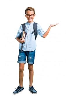 Corpo inteiro de menino estudante com mochila e óculos, segurando copyspace imaginário