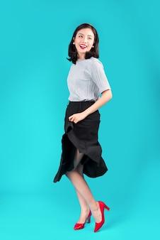 Corpo inteiro de mulher asiática sorridente, vestida com um vestido estilo pin-up sobre azul.