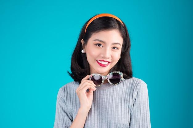 Corpo inteiro de mulher asiática sorridente, vestida com um vestido estilo pin-up, usando óculos sobre azul.