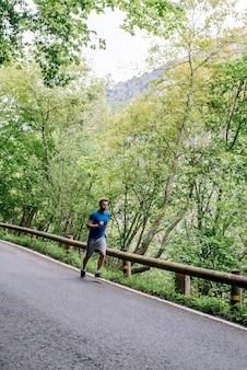 Corpo inteiro de um homem concentrado fazendo exercícios aeróbicos e correndo em uma estrada pavimentada contra árvores exuberantes
