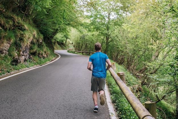 Corpo inteiro de um homem irreconhecível e focado fazendo exercícios aeróbicos e correndo em uma estrada pavimentada contra árvores exuberantes