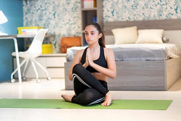 Corpo inteiro de uma adolescente concentrada e flexível em roupas esportivas, sentada na variação gomukhasana com as mãos de oração, enquanto pratica a atenção plena durante uma sessão de ioga em casa