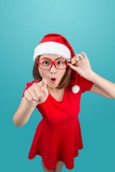 Corpo inteiro de uma atraente alegre garota asiática com chapéu de papai noel apontando com a mão para o espaço da cópia e sorrindo feliz