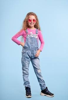 Corpo inteiro de uma garota sorridente em um macacão jeans elegante e óculos de sol rosa, olhando para a câmera em pé contra um fundo azul