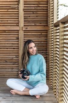 Corpo inteiro de uma jovem alegre, descalça, feminina, em roupas casuais, com uma câmera fotográfica nas mãos, sentada em um terraço de madeira