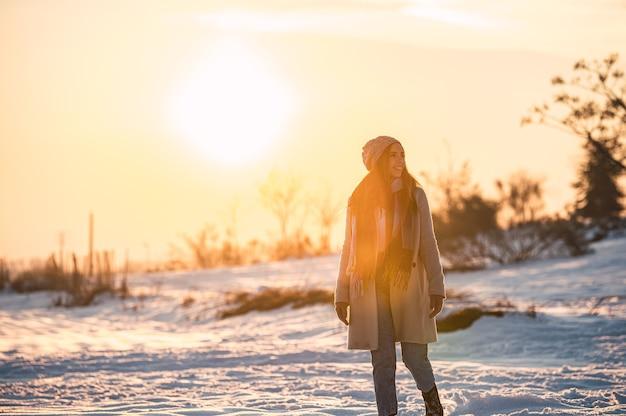 Corpo inteiro de uma jovem feliz em roupas quentes, passeando na neve branca e fresca na zona rural de inverno ao pôr do sol