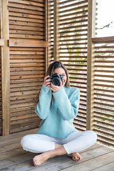 Corpo inteiro de uma jovem fotógrafa sorridente em roupa casual sentada em um terraço de madeira e tirando fotos com a câmera fotográfica enquanto aproveita o fim de semana ensolarado