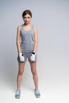 Corpo inteiro de uma linda boxeadora vestindo roupas esportivas e luvas praticando no estúdio sobre cinza