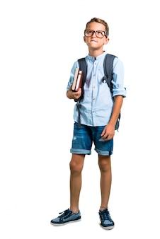 Corpo inteiro do menino do estudante com a trouxa e os vidros que têm dúvidas. de volta à escola