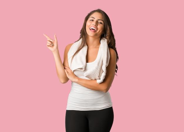 Corpo inteiro jovem fitness mulher curvilínea apontando para o lado com o dedo