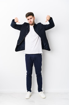 Corpo inteiro jovem homem caucasiano isolado mostrando o polegar para baixo e expressando antipatia.