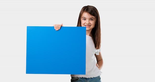Corpo inteiro menina alegre e motivada, mostrando um cartaz vazio onde você pode mostrar uma mensagem, o conceito de comunicação