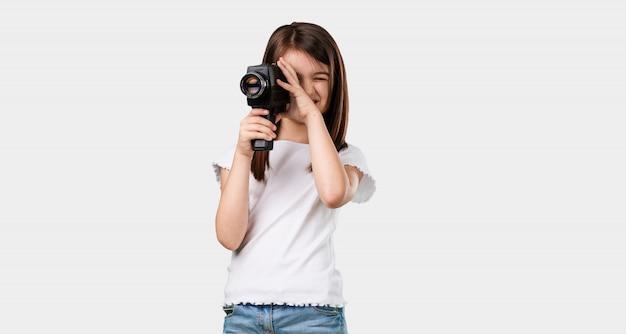 Corpo inteiro menina animada e entretida, olhando através de uma câmera de filme, à procura de um tiro interessante, gravando um filme, produtor executivo