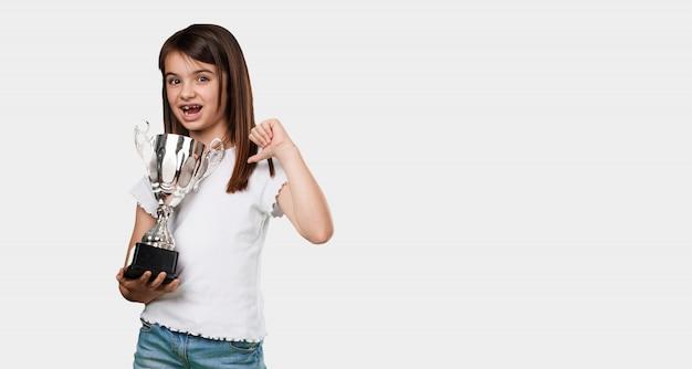 Corpo inteiro menina animado e enérgico, levantando um copo depois de ter conseguido uma vitória difícil, recompensa pelo trabalho duro, confiante e positivo
